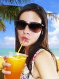 Mädchen, das ein orange gefrorenes Getränk trinkt Lizenzfreies Stockfoto