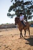 Mädchen, das ein Pferd in der Ranch reitet stockfoto
