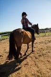 Mädchen, das ein Pferd in der Ranch reitet lizenzfreies stockbild