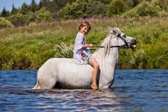 Mädchen, das ein Pferd in einem Fluss reitet Lizenzfreie Stockbilder