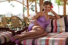 Mädchen, das ein purpurrotes Kleid legt auf ein Sofa trägt Lizenzfreie Stockfotografie