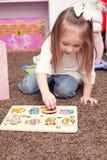 Mädchen, das ein Puzzlespiel zusammenfügt Stockbilder