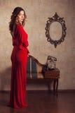 Mädchen, das ein rotes Kleid steht im Retro- Raum trägt Stockbilder