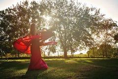 Mädchen, das in ein rotes Kleiderporträt spinnt stockbild