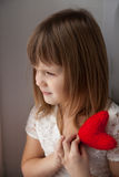 Mädchen, das ein rotes Knitherz und -wartung den Valentinstag Conc hält Stockfotos