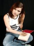 Mädchen, das ein Tagebuch schreibend denkt Stockfotografie