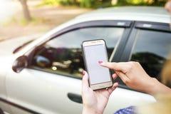 M?dchen, das ein Telefon im Hintergrund des Autos h?lt Themaautomiete unter Verwendung des Telefoncarsharings stockfoto