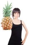 Mädchen, das eine Ananas (Fokus, anbietet auf Vordergrund) Stockfoto