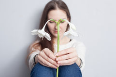 Mädchen, das eine Blume hält und unten traurig schaut Lizenzfreie Stockfotografie