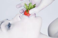 Mädchen, das eine Erdbeere isst lizenzfreies stockbild