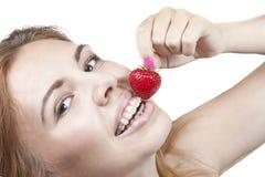Mädchen, das eine Erdbeere isst Stockbilder
