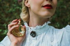 Mädchen, das eine Flasche Duftstoff anhält lizenzfreie stockbilder