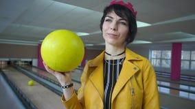 Mädchen, das eine gelbe Bowlingkugel hält stock footage