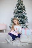 Mädchen, das eine Geschenkbox nahe dem Weihnachtsbaum hält Kind, das Weihnachtsgeschenk öffnet Stockfotografie