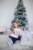 Mädchen, das eine Geschenkbox nahe dem Weihnachtsbaum hält Kind, das Weihnachtsgeschenk öffnet Stockfotos