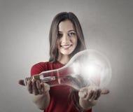 Mädchen, das eine Glühlampe hält lizenzfreie stockbilder