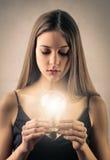 Mädchen, das eine Glühlampe hält stockbild