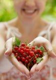 Mädchen, das eine Handvoll rote Johannisbeeren anhält Lizenzfreie Stockfotografie