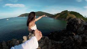 Mädchen, das eine Kerl ` s Hand auf einer Felsenklippe hält stock footage