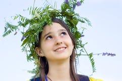 Mädchen, das eine Krone der Blumen trägt Stockfoto