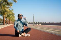 Mädchen, das eine Pause vom Training auf Laufbahn macht lizenzfreies stockfoto