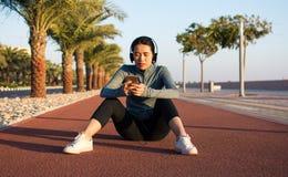 Mädchen, das eine Pause vom Training auf Laufbahn macht stockfotografie
