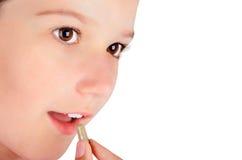 Mädchen, das eine Pillennahaufnahme isst Lizenzfreie Stockfotografie