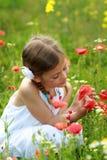 Mädchen, das eine rote Mohnblume betrachtet Stockfotografie