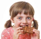 Mädchen, das eine Schokolade isst Lizenzfreies Stockfoto