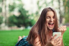 Mädchen, das eine sms Mitteilung mit guten Nachrichten in einem Handy empfängt stockbild