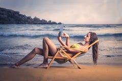 Mädchen, das eine Tablette am Strand verwendet Lizenzfreies Stockbild