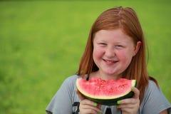 Mädchen, das eine Wassermelone isst lizenzfreie stockfotografie
