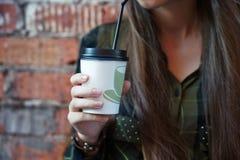Mädchen, das eine Wegwerfkaffeetasse hält Lizenzfreies Stockfoto