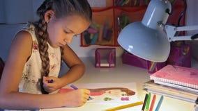 Mädchen, das eine Zeichnung am Schreibtisch färbt stock video