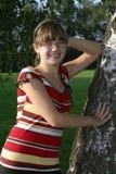 Mädchen, das an einem Baum sich lehnt. Stockbilder
