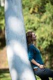 Mädchen, das an einem Baum sich lehnt Lizenzfreies Stockfoto