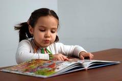 Mädchen, das in einem bunten Geschichtebuch schaut lizenzfreies stockfoto