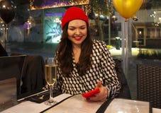 Mädchen, das in einem Café mit dem Handy sitzt stockfoto