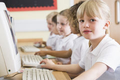 Mädchen, das an einem Computer an der Primärschule arbeitet Stockfotos
