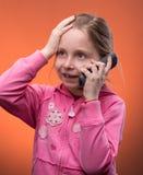 Mädchen, das an einem Handy spricht Stockbilder