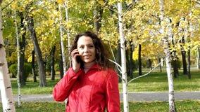 Mädchen, das an einem Handy im Park spricht stock video footage