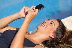 Mädchen, das an einem intelligenten Telefon auf einem Hotel Poolside auf Ferien simst stockfotografie