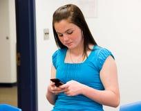 Mädchen, das in einem Klassenzimmer texting ist Stockbilder