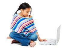 Mädchen, das an einem Laptop arbeitet Stockbild