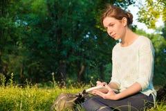 Mädchen, das in einem Park sitzt und in ein Notizbuch schreibt Stockfoto