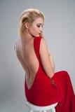 Mädchen, das in einem roten Kleid mit einem offenen Rücken und gespannt sitzt Lizenzfreies Stockbild