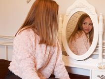 Mädchen, das in einem Spiegel schaut Lizenzfreie Stockfotografie