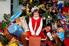 Mädchen, das in einem Stapel von den Weihnachtsgeschenken halten einen Kasten steht Stockfotos