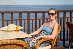 Mädchen, das in einem Stuhl auf der Terrasse durch das Meer sitzt Stockfoto