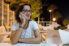 Mädchen, das an einem Tisch sitzt und auf dem Mobile auf einer Terrasse nachts spricht lizenzfreie stockbilder
